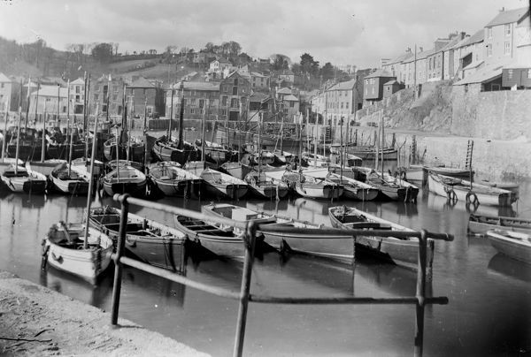 The inner harbour at Mevagissey looking towards the town with a large number of fishing vessels moored in the harbour, including FY6 'PETREL', FY49 and FY118. A car stands on the jetty near the town. Photographer: Unknown