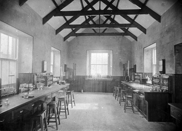 A view of the science laboratory of Probus School which was founded for the middle classes of Cornwall in 1852. The photograph shows work benches, stools and science equipment. Photographer: Frederick Ernest Argall