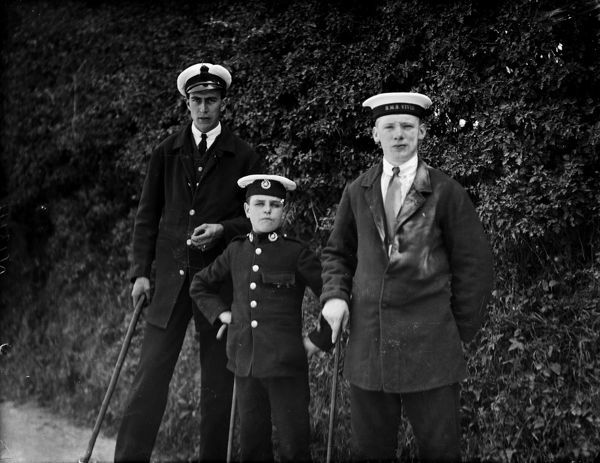 Two sailors and a young boy in a soldier's uniform all carrying walking sticks