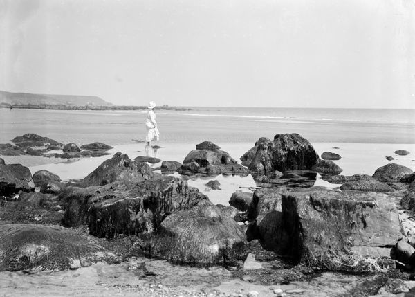 A lady paddling in a rock pool on the beach. Photographer: Herbert Hughes