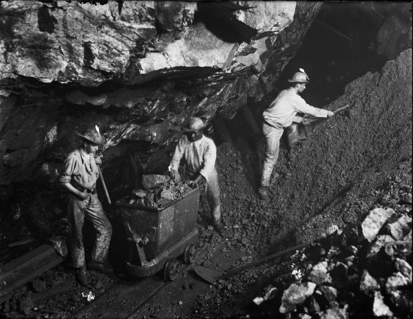 King Edward mine students working on Great Flat Lode transferring ore into trolley at 400 level. Around 1903. In 1897 part of the property was transferred to Camborne School of Mines as the (later) King Edward VII mine. Photographer: J.C. Burrow