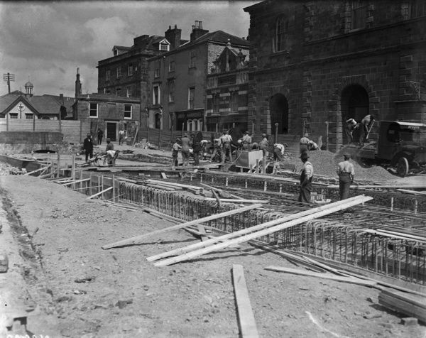 Workmen filling in Lemon Quay looking towards Lemon bridge and the old town hall which became the Hall for Cornwall in 1997. Photographer: Arthur William Jordan