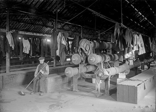 Interior of clothes dry. Miners' clothes hang on the walls and on racks above the heated pipes. Wooden boxes with lids secured with padlocks serve as a locker and seat. In the background behind the seated man a bicycle leans against a locker