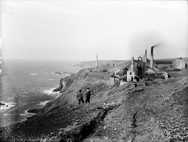 View of the Levant mine, looking towards Pendeen, before the building of the lighthouse. An old beam winding house can be seen in the centre foreground. Photographer: Unknown