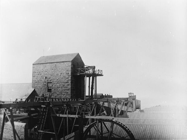 View of the Stamps engine house and a launder supplying water to a waterwheel. Photographer: Unknown