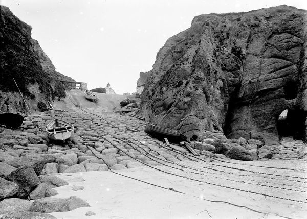 A view of fishing boats on the slipway looking towards the capstan in working order. The semi-natural caves can be seen to the right. Photographer: Possibly Herbert Hughes