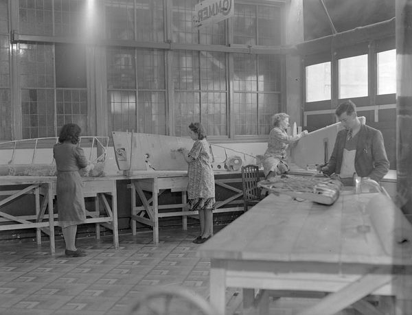 Workers in the aircraft component repair department during the Second World War. The workers are thought to be making parts for aircraft wings, probably for Spitfires, in what was the H.T.P. Motors showroom. Aircraft repair staff comprised 100 operatives