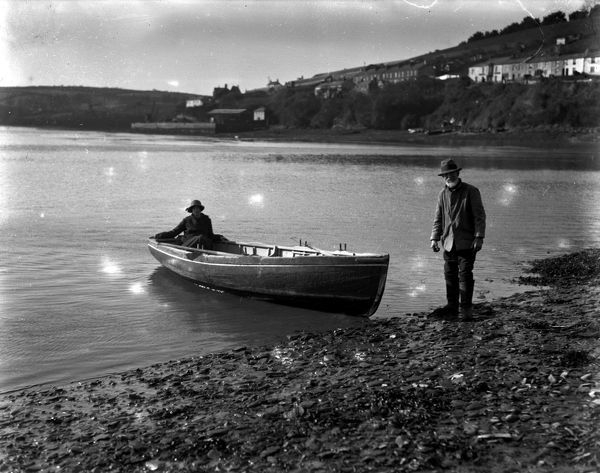 The ferryman and a woman passenger arriving on the foreshore. Malpas village can be seen in the background
