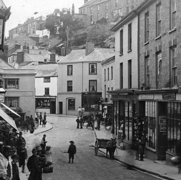 "Market Strand and the beginning of Market Street with No. 1, Truscotts the butchers, in the middle distance facing the camera. Taken in about 1894 from a series ""Towns through Cornwall - no. 21&quot"