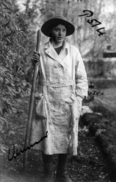 A member of the Women's Land Army standing in a field holding a pitchfork