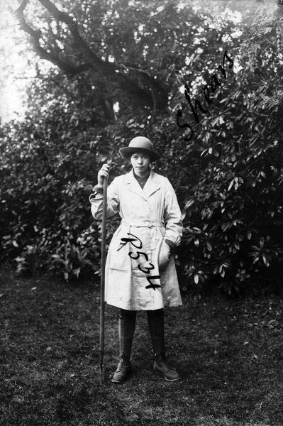 "A member of the Women's Land Army standing in a field and holding a long handled trowel. The name on the photograph is given as ""Shears"". The woman's uniform consists of boots, gaiters, felt hat and pale fabric overalls. Photographer"