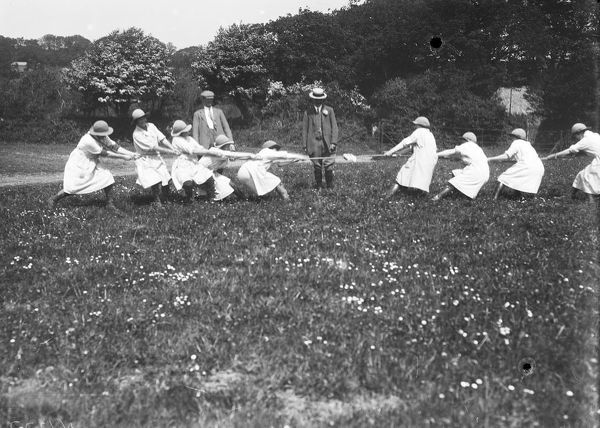 A group of the Women's Land Army taking part in a game of tug-of-war, umpired by two men, as part of their passing out celebrations at Tregavethan Farm, a Women's Land Army training centre. Photographer: Arthur William Jordan