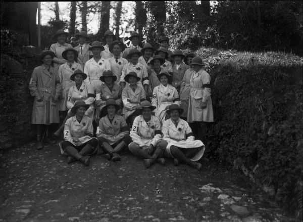 Twenty-four members of the Women's Land Army, pictured in a lane between two walls