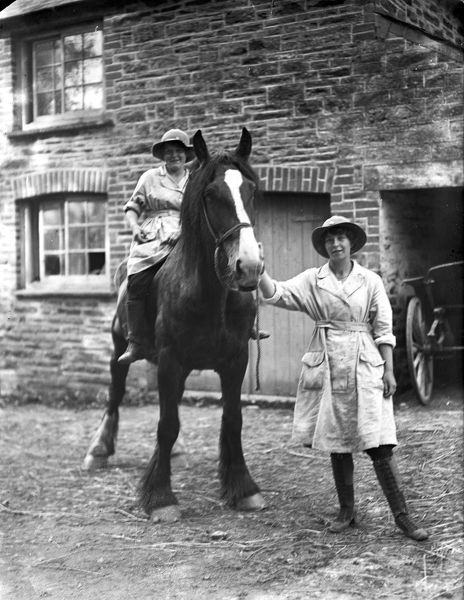 Two members of the Women's Land Army with a farm horse. Part of the farm house and wagon is visible behind them. The women's uniform consists of boots, gaiters, felt hats and pale fabric overalls. Photographer: Arthur William Jordan
