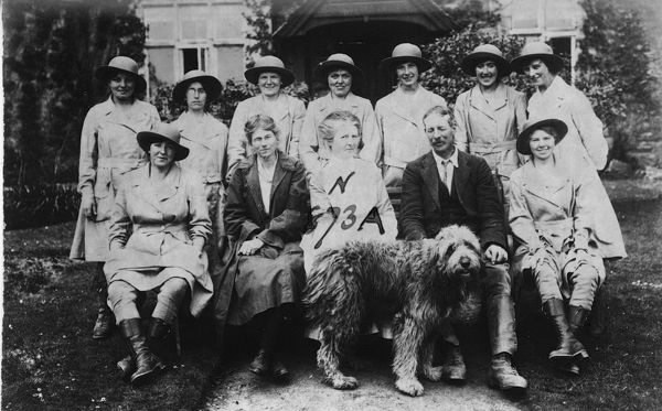 Nine members of the Women's Land Army pictured with the owners of Tregavethan Farm, a Women's Land Army training centre, and their dog. Back row, left to right: Ms. Brown, Mrs. Ford, Ms. Trejeweth, Ms. Nora Lock, possibly Ms. Vera Dunfrane, Ms