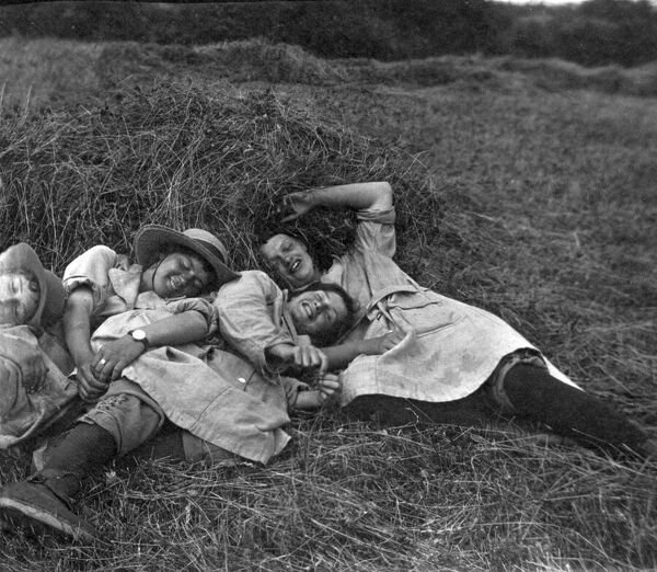 Four members of the Women's Land Army lying in a field against a small hay stack. Photographer: Arthur William Jordan