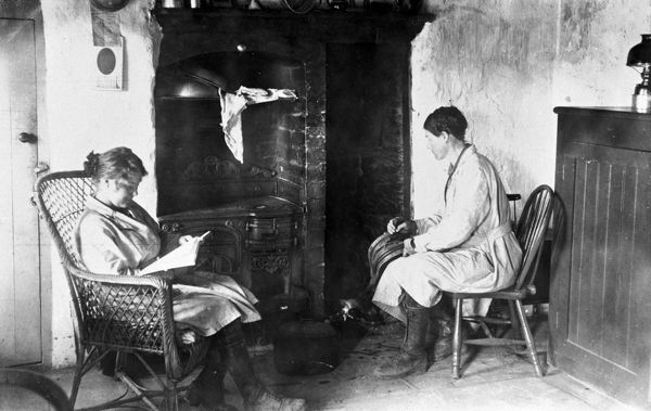 Two members of the Women's Land Army pictured in front of a Cornish Range and 'fringle' (bread-oven): one of the women is using the bellows to get the fire going to heat up a kettle or possibly the pot on the floor and the other is reading in a chair