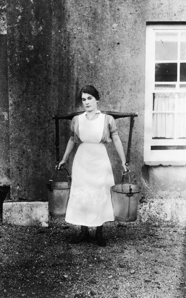 Dorothy Hoskin, a milkmaid carrying a yoke with two milk pails, during the First World War. Photographer: A. W. Jordan