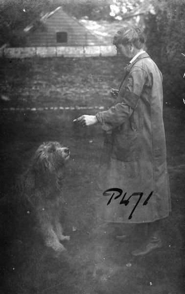 Mrs Alfred Martin, Tregavethan's owner, feeding the dog. Tregavethan was a Women's Land Army training centre during the First World War. Photographer: Arthur William Jordan