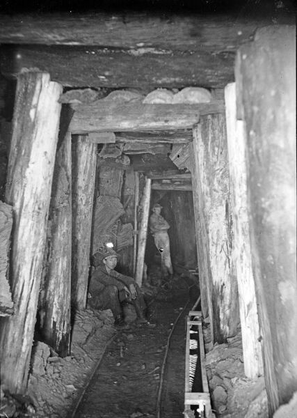 Two miners at the 400 fathom level. The miner in the foreground is seated with a candle on his hat, the other is standing in the background. Showing the timber supports and tramway. Photographer: Herbert Hughes