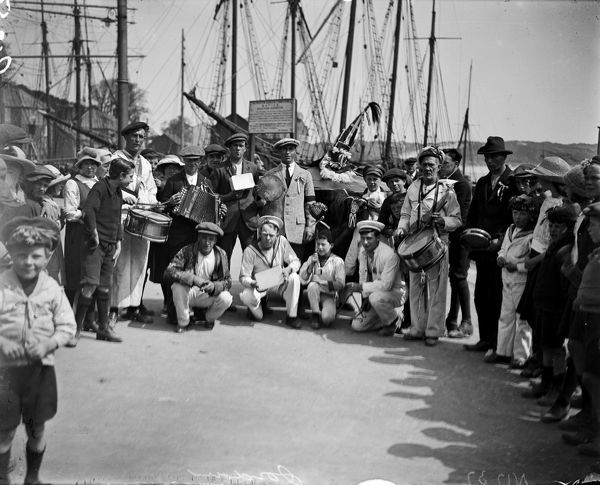 """Obby 'oss"" with band and sailors on the quay, Padstow. Photographer: Unknown"