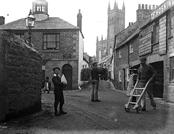 Onion Man (known as an Onion Johnny, if from France) with children and an employee of T. F. Hosking, manure, seed etc. merchant. The location is thought to be on the corner of Coinagehall Street with St. Mary's Church in the background. 1898