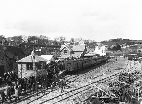 A crowd of excited onlookers surge over the tracks and onto the platform to witness the arrival of the first train, smoke billowing, on 27th March 1899, the grand opening day. The station was the western terminus of the North Cornwall Railway