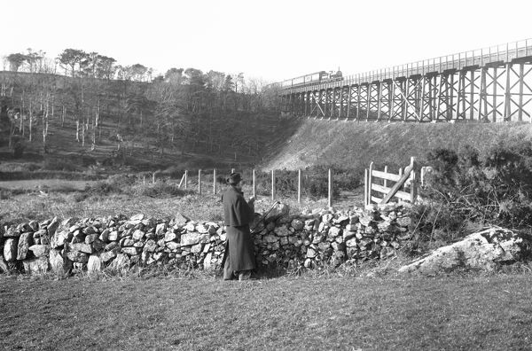 The original iron-girder viaduct at Penponds with a passing express train, watched by a man in the foreground. This viaduct was replaced with a stone viaduct which opened on the 3rd of September 1899. Photographer: Unknown
