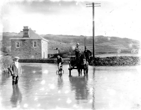 Flooded road with man wading through water. A horse and cart are in the road and a man standing on 2 chairs. Photographer: Arthur William Jordan