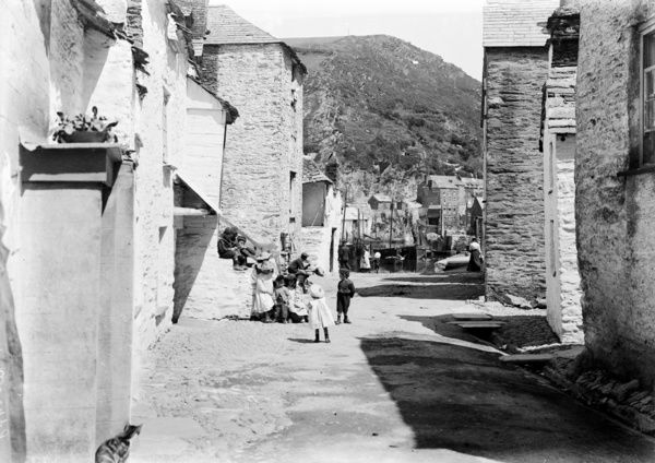 Children sitting on the steps, with a curious cat watching them. Harbour can be glimpsed in background