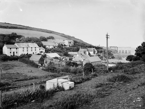 A general view of the east side of Porthoustock with the stone quarry quay in the background, taken from inland. The lifeboat house can be seen to the right of centre. Photographer: John Charles Burrow