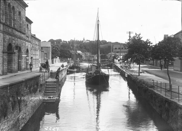 A view from Lemon Bridge with the River Kenwyn at high tide. Truro school stands on the hill in the background. Sailing barges, one with wooden square engine housing towards the stern, are alongside both quays while another is moored mid stream