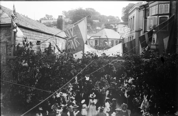 Street scene, with people seated at trestle tables, having tea. Overhead, the streets are decorated with greenery and flags. A 'V R' for Queen Victoria can be seen, backwards