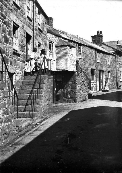 A view of Back Road, with Ann Clarke's house on the left. Poster for carnival & regatta dated Monday 21st August 1899 posted on a wooden door below a woman and two children standing at the top of the steps outside the front door of Ann Clarke's house
