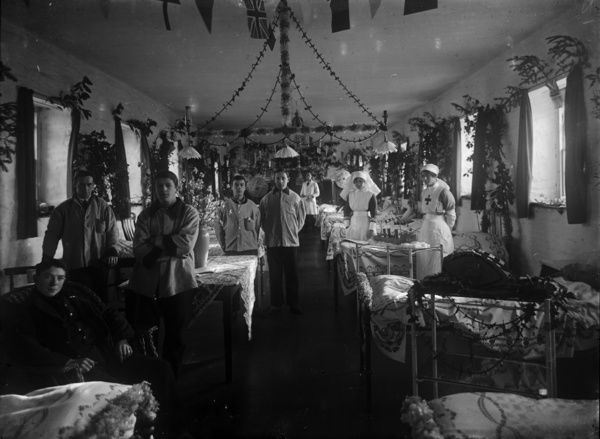 Red Cross nurses and patients in unnamed ward, decorated for Christmas 1917. On the table front left is a hand-made model of a tank. Names of the patients and nurses are unknown. Photographer: A.W. Jordan