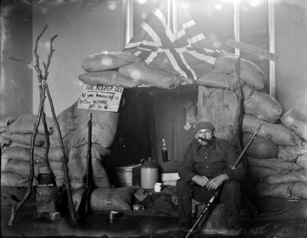 One service man in Chellew Ward with a trench scene set up. The notice reads The better 'ole if you know of a better ward go to it. Probably Christmas 1918. Photographer: A.W. Jordan