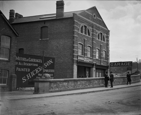 S. Hicks & Son Garage, by Boscawen Bridge, an authorised Ford dealer for motors and carriages of all descriptions. Two well dressed men wearing bowler hats are chatting in the street. Photographer: A.W. Jordan