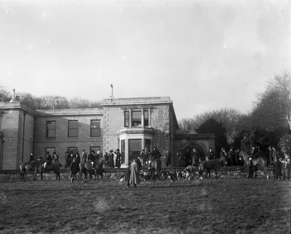 A Hunt meet at Scorrier House. Horses and beagles can be seen on the lawn in front of the ha-ha or terrace with the house behind. It was probably taken before the 1908 fire. Photographer: Arthur William Jordan