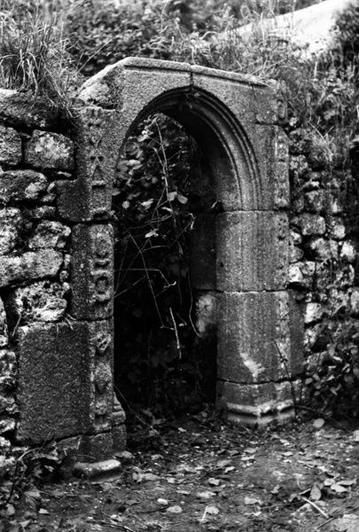 Doorway remains at Trewoofe, St Buryan, Cornwall. The house was demolished in 1918, but the doorway was later used at Ayr, St Ives, and has since been returned to Trewoofe. Photographer: Herbert Hughes