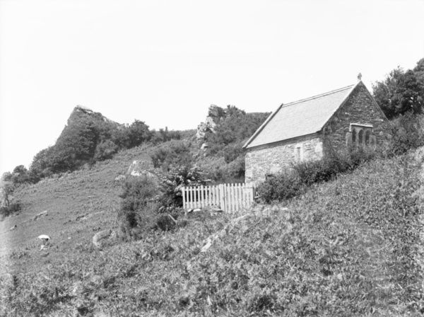 A general view of St Clether Chapel. A lady is seated on the bank to the left hand side, holding a parasol. Photographer: Herbert Hughes