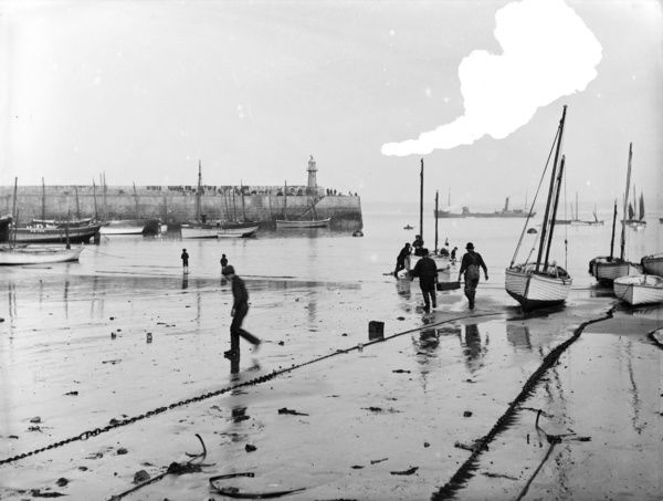 Harbour looking seaward at low tide with fishing boats and fishermen on tideline. Smeaton's pier to the left. There is a steam ship amongst the fishing boats just outside the harbour wall. Photographer: Herbert Hughes