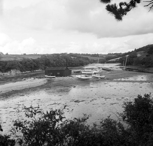The creek at St Just in Roseland with various motor and sailing boats drawn up on the mud alongside a shed. Photographer: Charles Woolf
