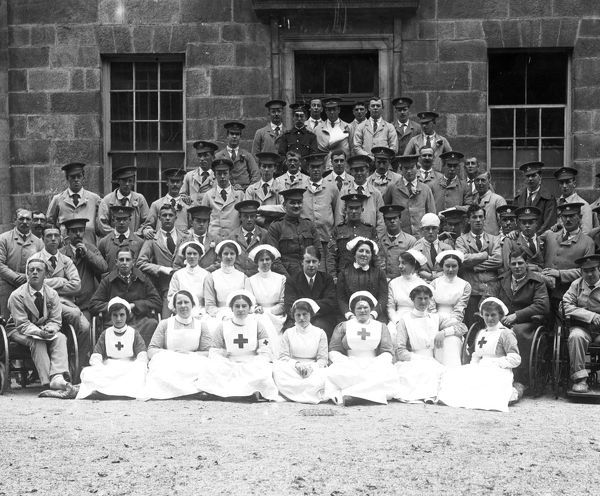 Nurses, including Red Cross nurses, and patients, some in military uniform, four of them wheelchair-bound, posing in a large group outside the Infirmary. Photographer : A W Jordan, 21 July 1916