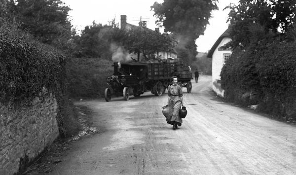 A traction engine pulling a heavy load going for water opposite the Wheel Inn. A woman carries pitchers in the foreground. Photographer: Unknown