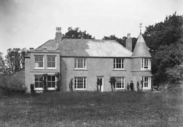 The exterior of Tregorland House with a man and young boy standing by a window. Photographer: Arthur William Jordan