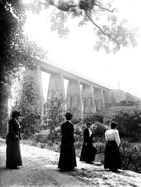 View of the viaduct taken from Trenance Gardens, with four women, wearing straw boaters, standing in the foreground. Photographer: Unknown