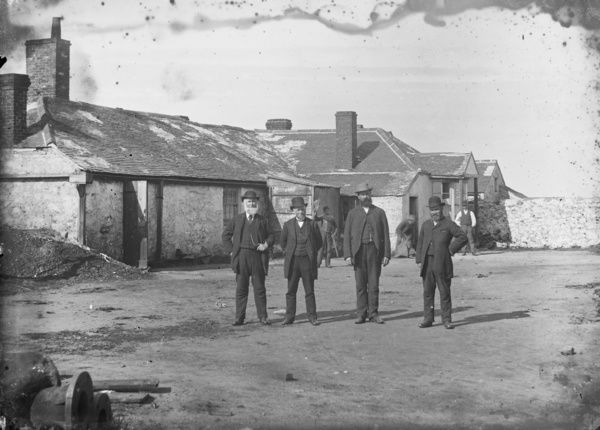 Mine Captains outside the Count House. Possibly the Wheal Sisters section of the mine. The Captains are left to right, Mr. Rosewarne, N. Richards, Symon Thomas and unknown