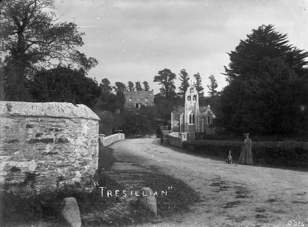 View over Tresillian Bridge to Holy Trinity Church in the distance. A gentleman artist with easel is also on the bridge. The church was built as a mission church in 1878. It was extended and the bell tower added in 1904 when it became a parish church