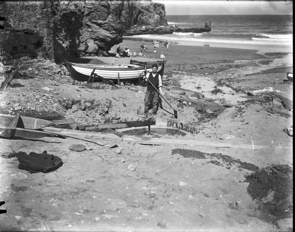 Tin streamer working a buddle, a circular pit used to separate by sedimentation minerals from rock dust in crushed ore, on the beach at Trevaunance Cove, St Agnes, Photographer: Arthur William Jordan