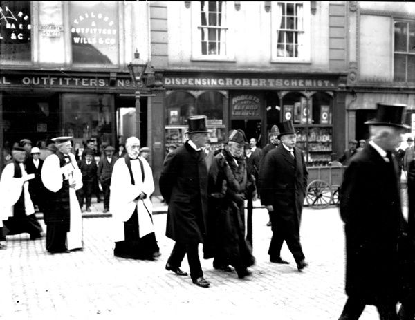 Mayor and church dignitaries in procession passing Robert's chemist shop and Wills & Co general outfitters. Photographer: Arthur William Jordan